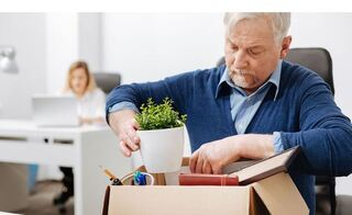 Laid off Older Worker packing up his desk